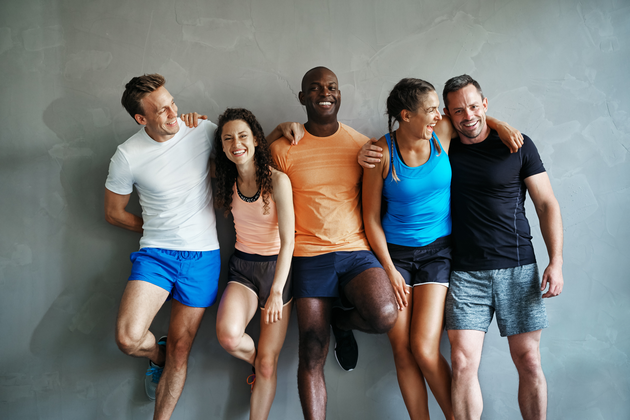 Smiling group of friends in sportswear laughing together while standing arm in arm in a gym after a workout